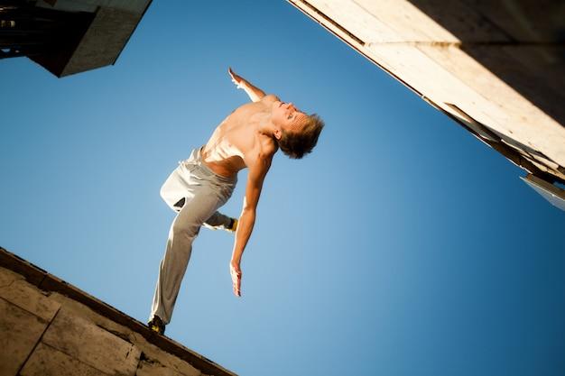 Jonge mens die en parkour tussen gebouwen buiten op duidelijke de zomerdag met blauwe hemel springen uitoefenen