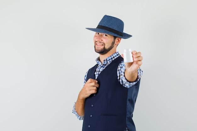 Jonge mens die fles pillen in overhemd, vest, hoed toont en vrolijk kijkt