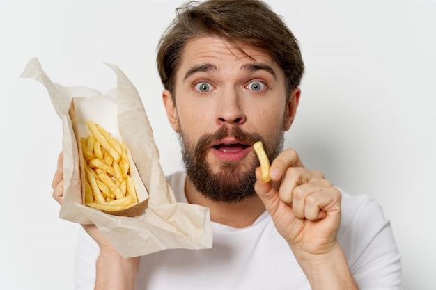 Jonge mens die frieten eet