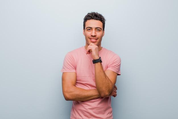 Jonge mens die gelukkig en met hand op kin glimlachen glimlachen, of een vraag benieuwd zijn stellen, opties vergelijken met grijze muur