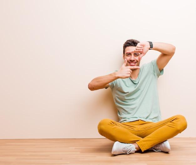 Jonge mens die gelukkig, vriendschappelijk en positief voelt, glimlachend en een portret of fotokader maakt met handen die op de vloer zitten