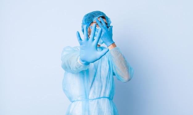 Jonge mens die gezicht behandelt met hand en andere hand vooraan zet om camera tegen te houden, foto's of afbeeldingen weigert. coronavirus concept