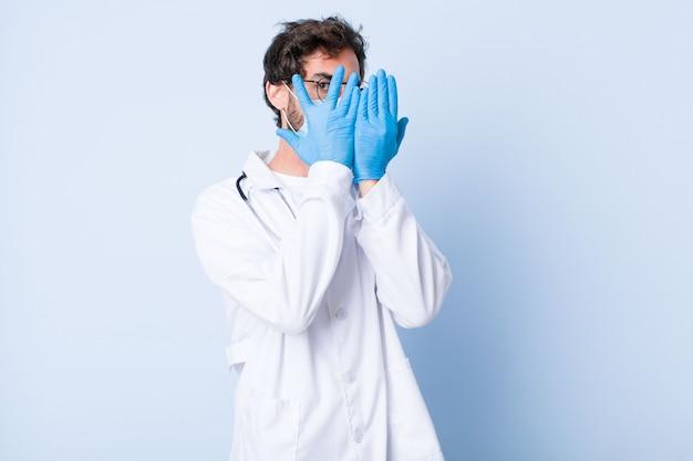 Jonge mens die gezicht behandelt met handen, die tussen vingers met verrast uitdrukking gluren en aan de kant kijkt. coronavirus concept