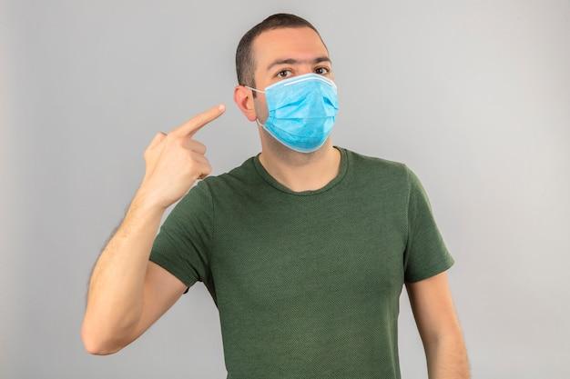 Jonge mens die gezichts medisch masker draagt dat aan zich met vinger op geïsoleerd wit richt