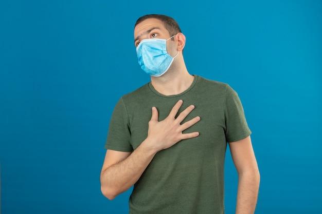 Jonge mens die gezichts medisch masker hard aan ademhaling dragen terwijl wat betreft zijn borst met hand op blauw wordt geïsoleerd