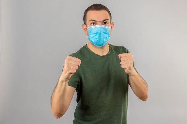 Jonge mens die gezichts medisch masker met boos gezicht dragen die zich met in dozen doende vuisten bevinden, en klaar aan te vallen geïsoleerd op wit