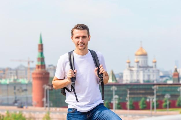 Jonge mens die glimlachend gelukkig portret wandelen. mannelijke wandelaar die in de stad loopt