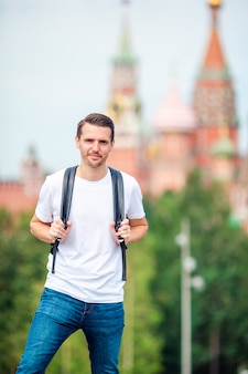 Jonge mens die glimlachend gelukkig portret wandelt. mannelijke wandelaar die in de stad loopt