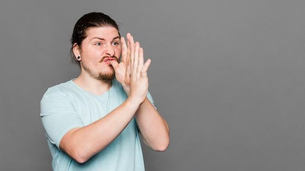 Jonge mens die het gebaar van de handtrompet tegen grijze achtergrond maakt