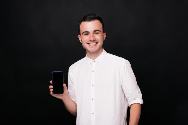 Jonge mens die het lege scherm van zijn telefoon op zwarte achtergrond toont die iets adverteert.