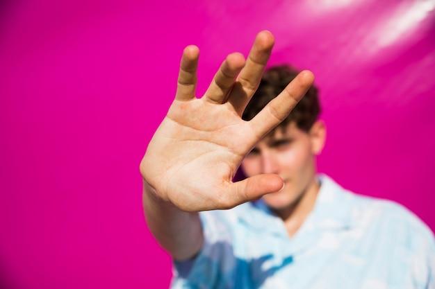 Jonge mens die het zonlicht met hand tegenhoudt