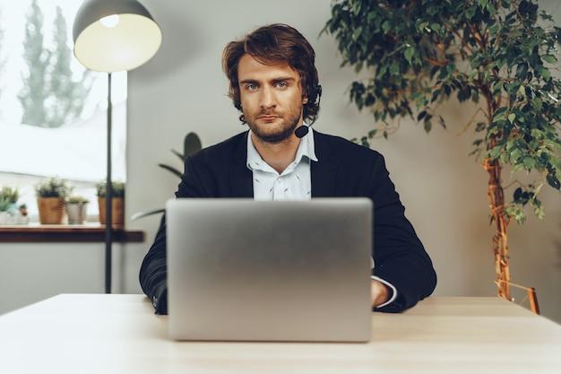 Jonge mens die hoofdtelefoon draagt die een videogesprek door laptop doet