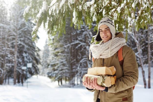 Jonge mens die hout in bos verzamelt
