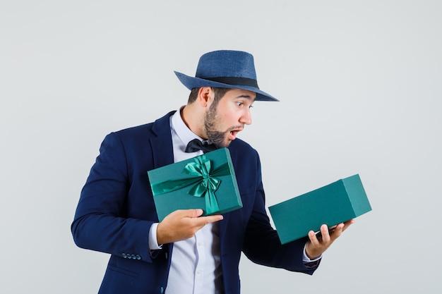 Jonge mens die huidige doos in kostuum, hoed onderzoekt en verbaasd, vooraanzicht kijkt.