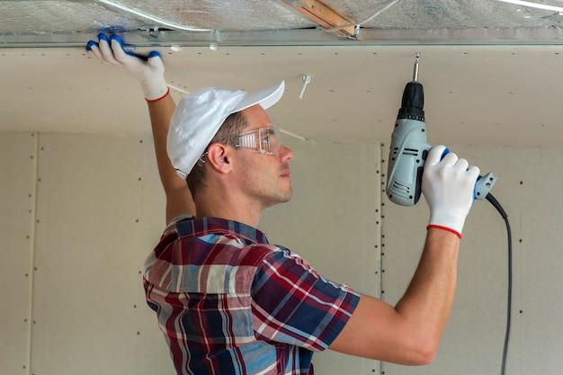 Jonge mens die in beschermende brillen gipsplaat opgeschort plafond bevestigen