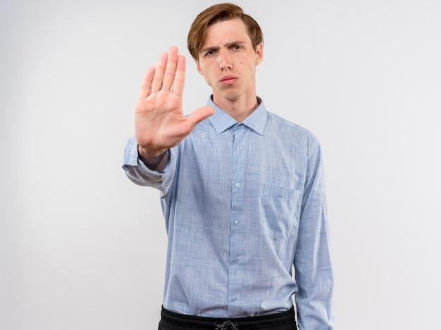 Jonge mens die in blauw overhemd stopteken met open hand met ernstig gezicht maakt dat zich over witte muur bevindt