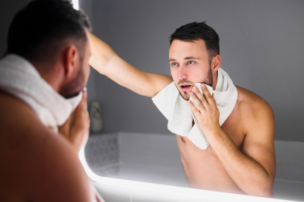 Jonge mens die in de badkamersspiegel kijkt