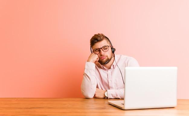 Jonge mens die in een call centre werkt dat droevig en peinzend voelt, bekijkend exemplaarruimte.