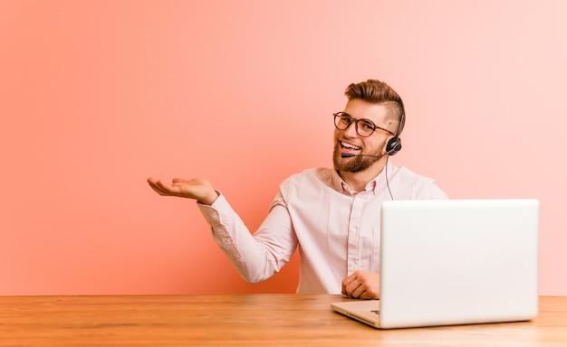 Jonge mens die in een call centre werkt dat een exemplaarruimte op een palm toont en een andere hand op taille houdt.