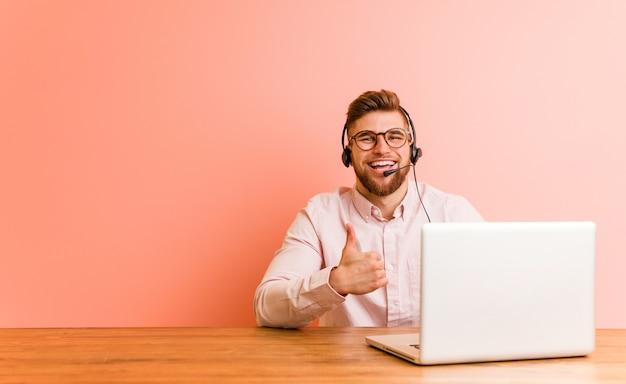 Jonge mens die in een call centre werkt dat en duim glimlacht opheft