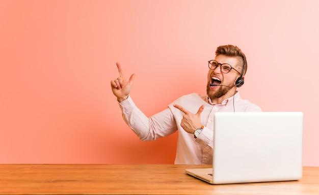 Jonge mens die in een call centre werkt dat met wijsvingers aan een exemplaarruimte richt, opwinding en wens uitdrukt.