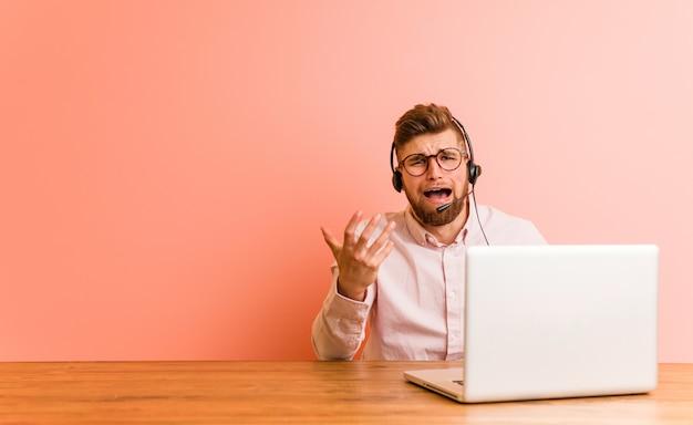 Jonge mens die in een call centre werkt dat met woede gilt.