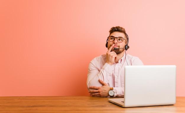 Jonge mens die in een call centre werkt dat zijdelings met twijfelachtige en sceptische uitdrukking kijkt.