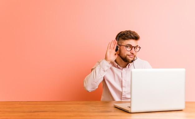 Jonge mens die in een call centre werkt die aan een roddel probeert te luisteren.