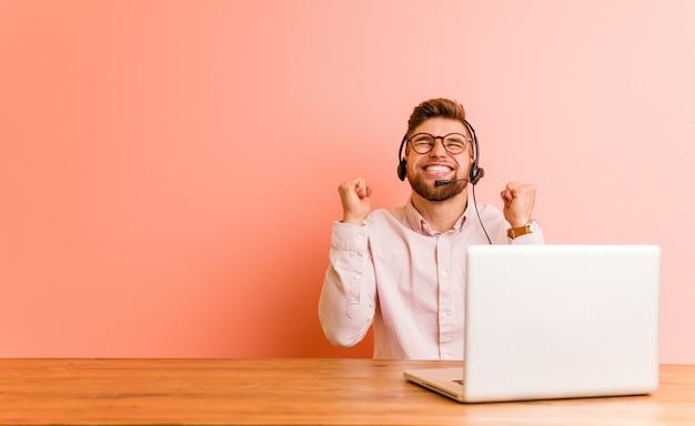 Jonge mens die in een call centre werkt die vuist opheft, gelukkig en succesvol voelt. overwinning concept.