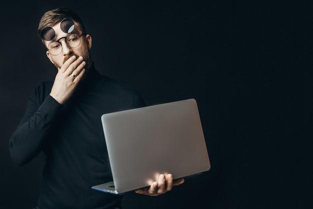 Jonge mens die in flip-up glazen laptop houdt bekijkend het met schok op zwarte muur