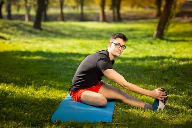 Jonge mens die in glazen yoga in openlucht opleiden. sportieve man maakt ontspannende oefening op een blauwe yogamat, in park. kopieer ruimte