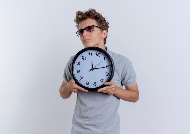 Jonge mens die in grijs poloshirt muurklok toont die verward opzij kijkt die zich over witte muur bevindt