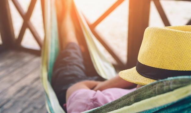 Jonge mens die in hangmat bij zonnig strand door oceaan en slaapt ligt. hij hield op gezicht. jonge man koelen.