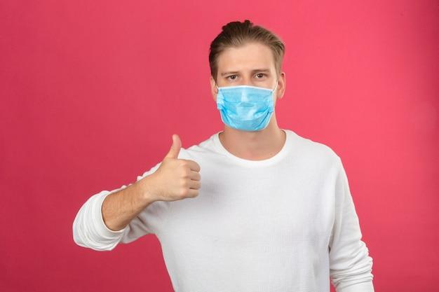 Jonge mens die in medisch beschermend masker camera bekijkt die duimen toont die zich over geïsoleerde roze achtergrond bevinden