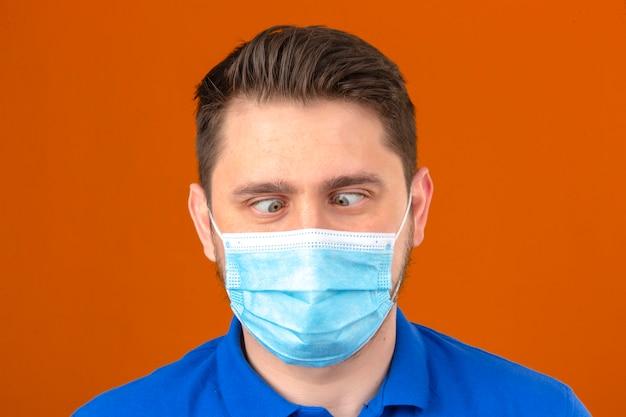 Jonge mens die in medisch beschermend masker grimas maakt die zijn ogen kruist over geïsoleerde oranje muur