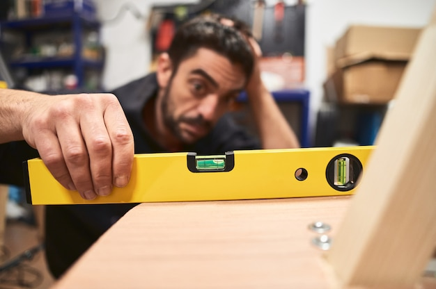 Jonge mens die in zijn garage werkt die een houten raadsstructuur controleert met een bellenniveau met een ongerust gemaakte uitdrukking