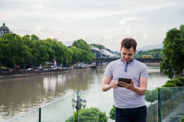 Jonge mens die informatie zoekt die een tabletcomputer met behulp van.