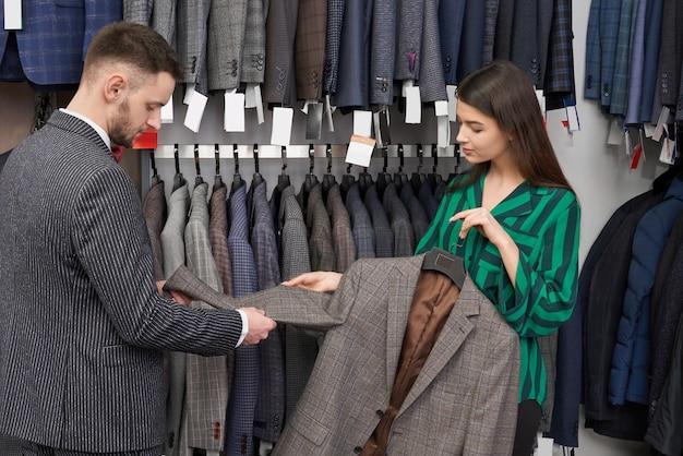 Jonge mens die jasje in winkel met medewerker kiezen.