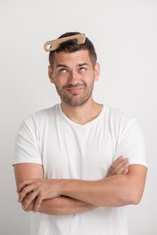 Jonge mens die kam bekijkt die in zijn haar wordt geplakt dat zich tegen witte achtergrond bevindt