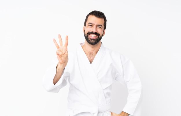 Jonge mens die karate gelukkig doet en drie met vingers telt