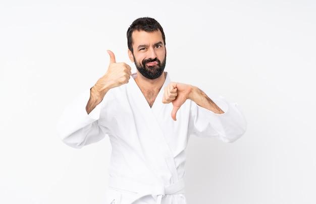 Jonge mens die karate over geïsoleerd wit doet dat goed-slecht teken maakt. onbeslist tussen ja of niet