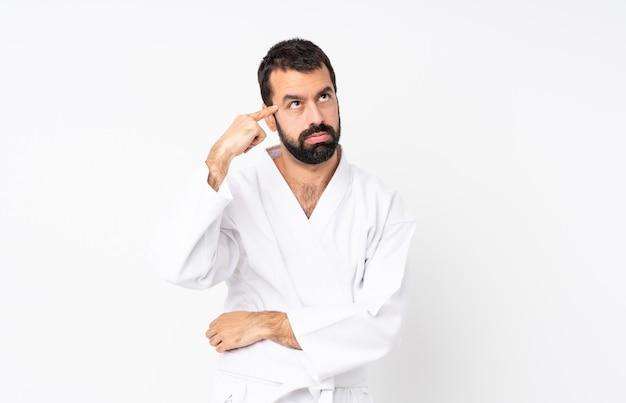Jonge mens die karate over geïsoleerd wit doet dat het gebaar van waanzin maakt die vinger op het hoofd zet