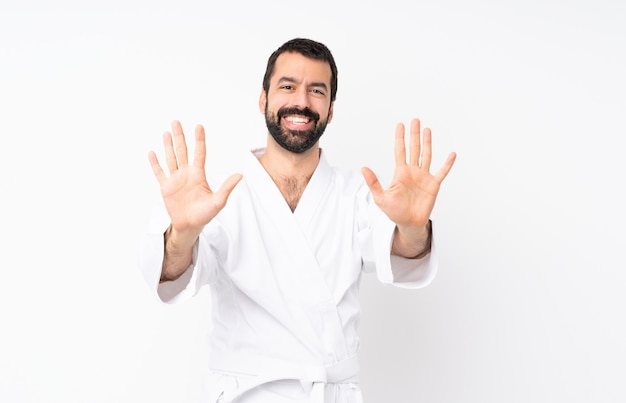 Jonge mens die karate over geïsoleerd wit doet die tien met vingers tellen