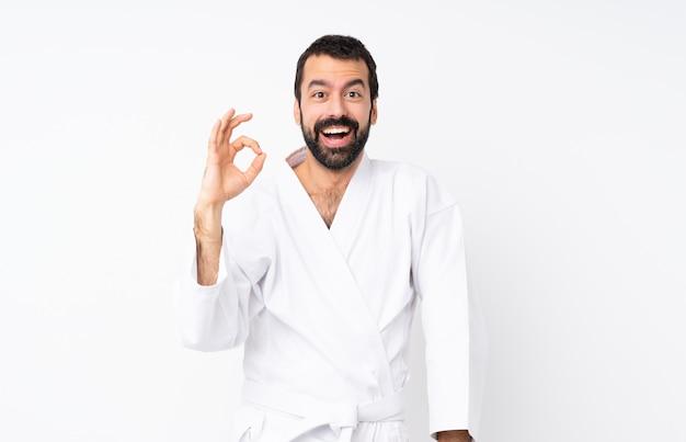 Jonge mens die karate over geïsoleerd wit doet verrast en ok teken toont