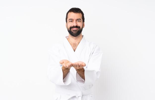 Jonge mens die karate over geïsoleerde holding doet denkbeeldig op de palm denkbeeldig om een advertentie op te nemen