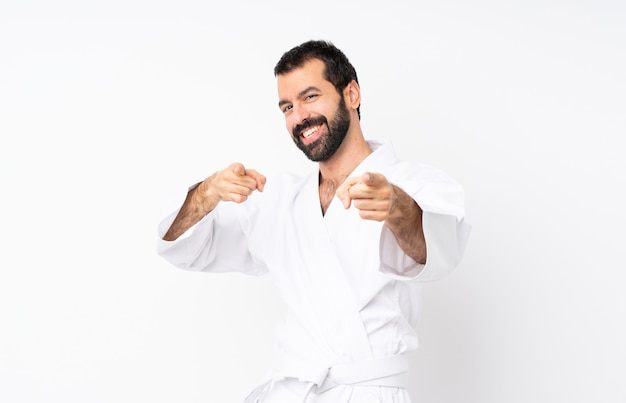 Jonge mens die karate over geïsoleerde puntenvinger naar u doet terwijl het glimlachen