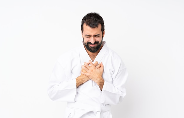 Jonge mens die karate over geïsoleerde witte achtergrond doet die pijn in het hart heeft