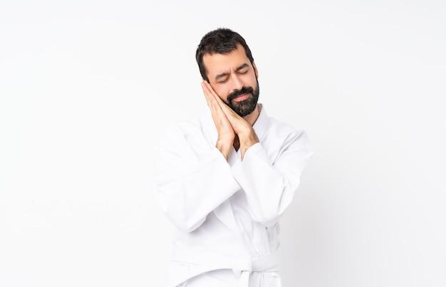 Jonge mens die karate over geïsoleerde witte achtergrond doet die slaapgebaar in aanbiddelijke uitdrukking maakt
