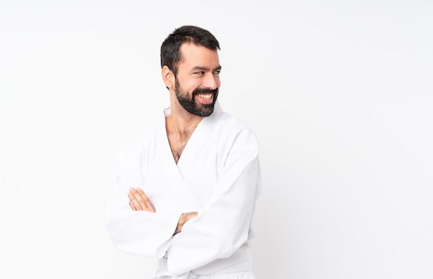 Jonge mens die karate over geïsoleerde witte achtergrond met gekruiste en gelukkige wapens doet