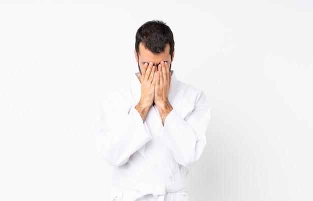 Jonge mens die karate over geïsoleerde witte achtergrond met vermoeide en zieke uitdrukking doet